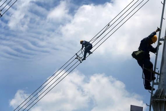 Công nhân vận hành lưới điện Trung Quốc Southern Power Grid kiểm tra cáp điện. Ảnh: Reuters.