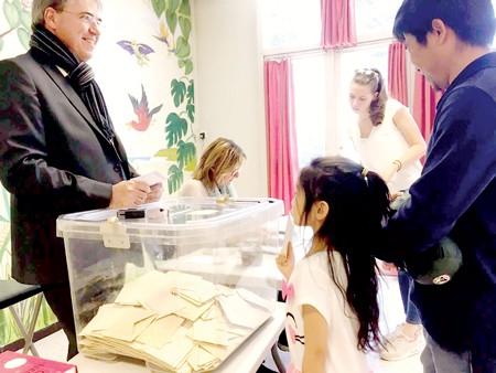Bố con anh Đoàn Trung đi bầu vòng 1 tại một điểm bỏ phiếu ở TP Aix-en-Provence, miền Nam nước Pháp