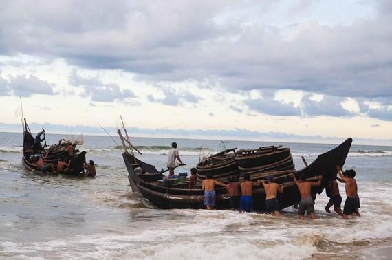 Ngư dân đẩy thuyền ra khơi sau cơn bão vừa tan