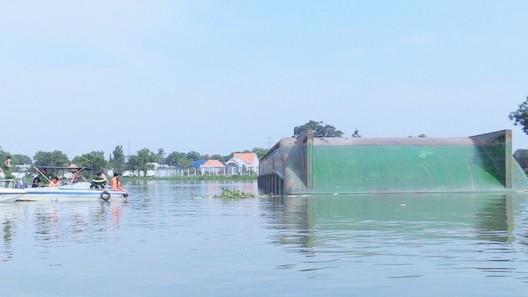 Lực lượng tìm kiếm xung quanh chiếc sà lan bị lật úp đề tìm người mất tích dưới sông. Ảnh: TTXVN