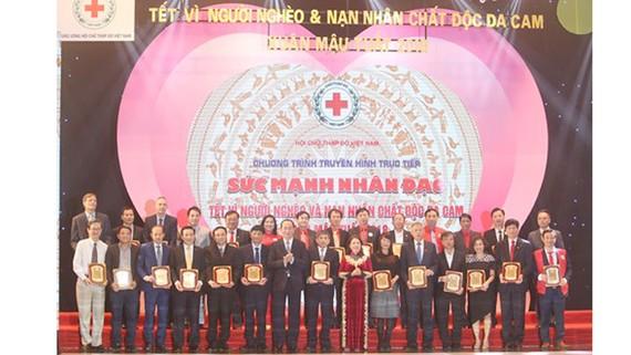 Chủ tịch nước Trần Đại Quang trao bảng vàng danh dự tặng các cụm thi đua khu vực, doanh nghiệp, tổ chức tham gia tặng quà Tết trong chương trình. Ảnh: QĐND