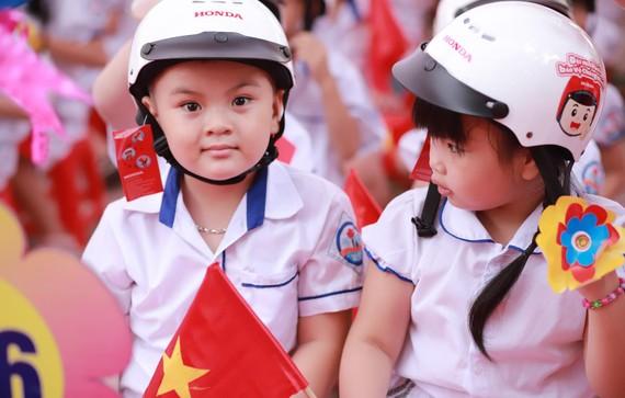 Niềm vui của các em nhỏ nhân khi nhận được mũ bảo hiểm nhân ngày khai giảng