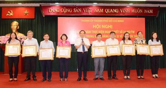 Đồng chí Trần Lưu Quang, Phó Bí thư Thường trực Thành ủy TPHCM  trao Bằng khen cho các tập thể. Ảnh: hcmcpv
