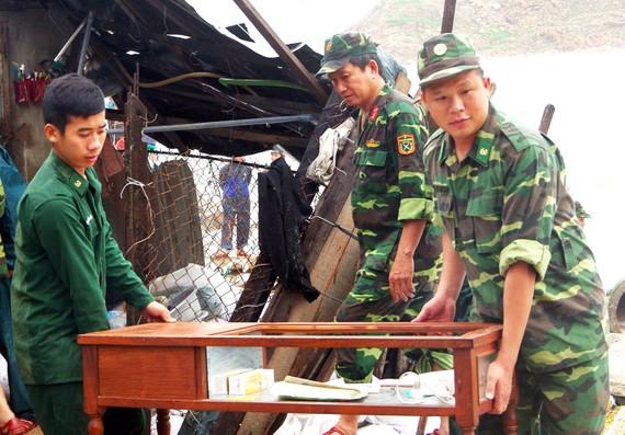 Chiến sĩ bộ đội biên phòng tỉnh Bình Định hỗ trợ người dân khắc phục hậu quả sau bão. Ảnh: XUÂN HUYÊN