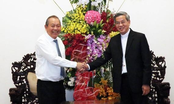 Phó Thủ tướng Thường trực Trương Hòa Bình trao lẵng hoa của Tổng Bí thư, Chủ tịch nước Nguyễn Phú Trọng chúc mừng Tổng Giám mục Giuse Nguyễn Năng. Ảnh: TTXVN