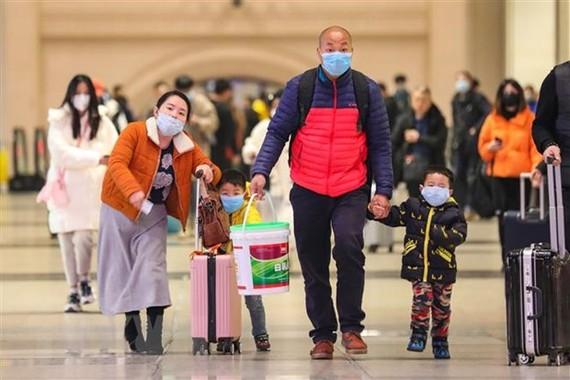 Hành khách đeo khẩu trang khi di chuyển tại một nhà ga ở Hồ Bắc, Trung Quốc để phòng tránh lây nhiễm dịch bệnh viêm phổi do virus corona ngày 21-1-2020. Nguồn: AFP/TTXVN