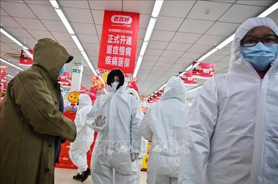 Nhân viên mặc quần áo bảo hộ và khẩu trang phòng chống dịch bệnh viêm phổi lạ do nhiễm virus corona phục vụ khách hàng tại một nhà thuốc ở Vũ Hán, Trung Quốc, ngày 25/1. Ảnh: AFP/TTXVN