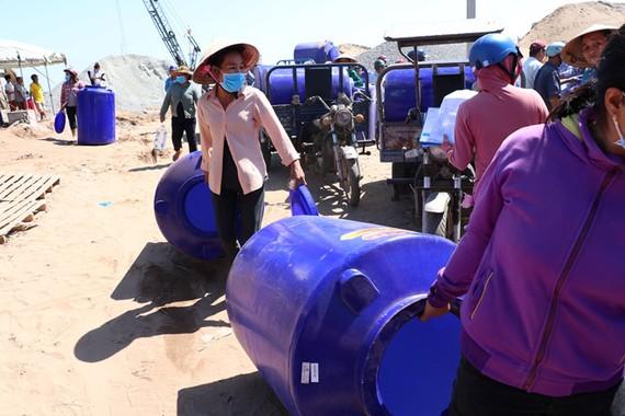 Người dân Bến Tre phấn khởi mang dụng cụ chứa nước về nhà. Ảnh: Bắc Bình (Báo Thanh Niên)