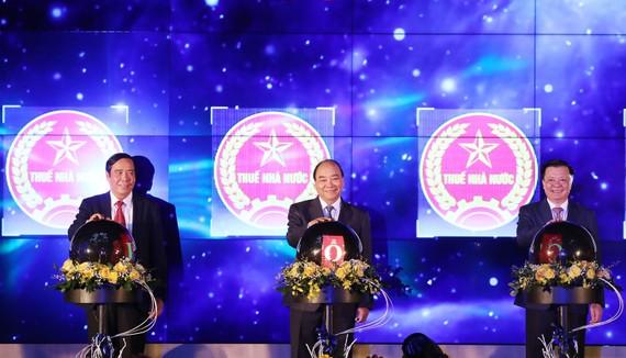 Thủ tướng Nguyễn Xuân Phúc thực hiện nghi thức hòa mạng các chi cục thuế khu vực vào hệ thống quản lý thuế chung cả nước. Ảnh: TTXVN
