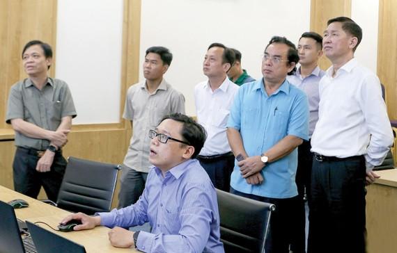 Phó Chủ tịch UBND TPHCM Trần Vĩnh Tuyến cùng Chủ tịch UBND tỉnh Bạc Liêu Dương Thành Trung theo dõi các mô hình quản lý đô thị thông minh tại TPHCM. Ảnh: HOÀNG HÙNG