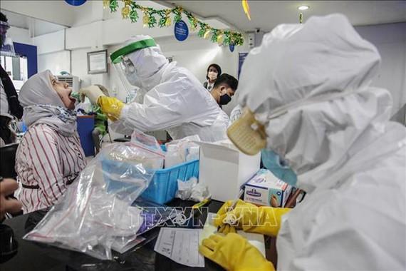 Nhân viên y tế lấy mẫu dịch xét nghiệm Covid-19 cho người dân tại Medan, Indonesia, ngày 10-6-2020. Ảnh: THX/TTXVN