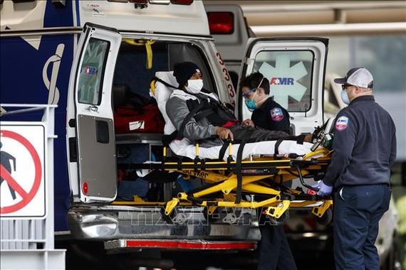 Nhân viên y tế chuyển bệnh nhân nhiễm Covid-19 tới bệnh viện Trường đại học George Washington ở Washington DC. Ảnh: THX/TTXVN