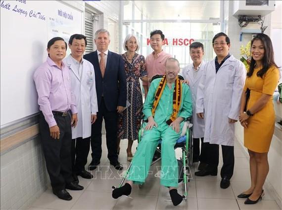 Bệnh nhân 91 chụp ảnh lưu niệm với đại diện Lãnh sự quán Anh tại Thành phố Hồ Chí Minh và các y bác sỹ trong ngày xuất viện sáng 11-7. Ảnh: TTXVN
