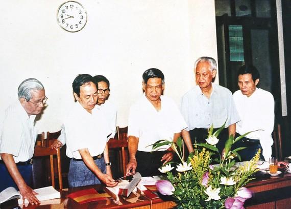 """Đồng chí Lê Khả Phiêu (giữa) cùng các đồng chí trong Hội đồng Xuất bản Văn kiện Đảng duyệt bìa bộ sách """"Văn kiện Đảng toàn tập"""", năm 1998. Ảnh tư liệu"""