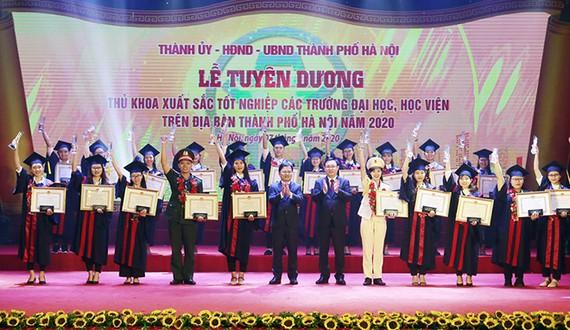 Bí thư Thành ủy Hà Nội Vương Đình Huệ trao bằng khen cho các thủ khoa xuất sắc. Ảnh: CAND