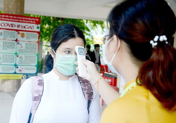 Giáo viên Trường THPT Phan Châu Trinh (quận Hải Châu, TP Đà Nẵng) kiểm tra thân nhiệt cho học sinh trước khi vào lớp. Ảnh: XUÂN QUỲNH