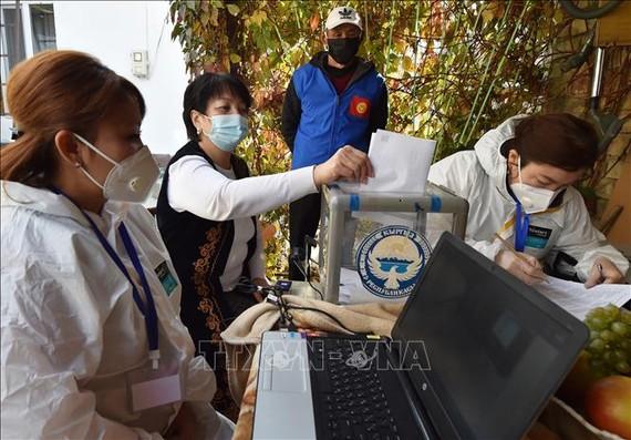 Cử tri bỏ phiếu tại một địa điểm bầu cử ở Bishkek, Kyrgyzstan. Ảnh: AFP/TTXVN