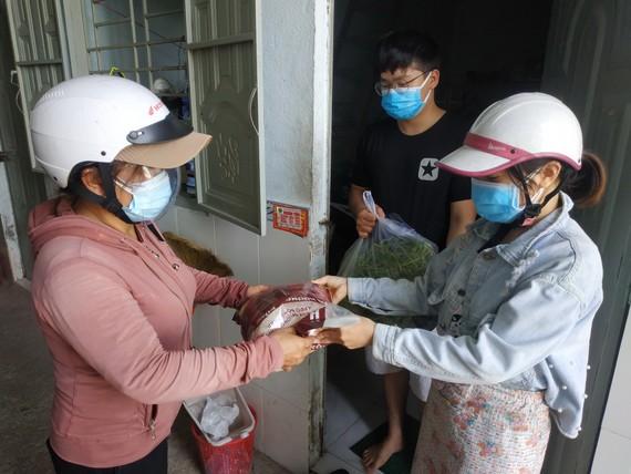 Công nhân ở khu trọ Tổ 5A nhận quà hỗ trợ từ đại diện UBND phường Tăng Nhơn Phú B (TP Thủ Đức). Ảnh: MINH NGHĨA