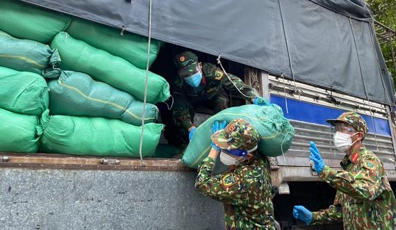 Bộ đội bốc dỡ gạo, thực phẩm, nhu yếu phẩm cung ứng đến các phường tại quận 6, sáng 28-8. Ảnh: CAO THĂNG