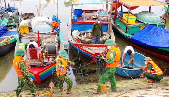 Bộ đội Biên phòng Hà Tĩnh giúp ngư dân neo đậu tàu thuyền. Ảnh: DƯƠNG QUANG