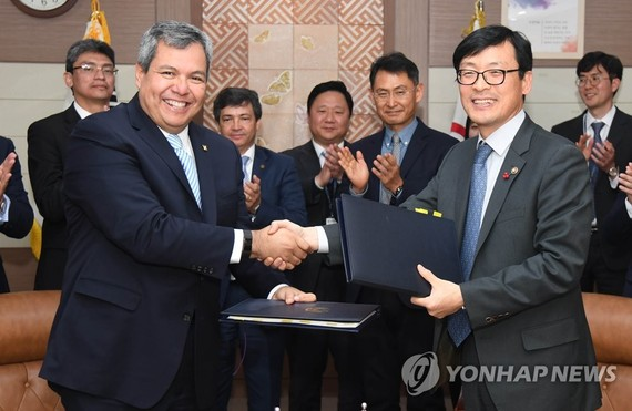 This photo provided by the Ministry of Economy and Finance shows Vice Minister Lee Ho-seung (R) shaking hands with Dante Mossi, executive president of the Central American Bank for Economic Integration, during a signing ceremony at the government complex