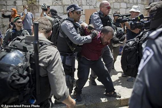 Cảnh sát Israel bắt giữ một người Palestine sau khi ông này kêu gọi các giáo sĩ cầu nguyện trên phố thay vì tại nhà thờ Hồi giáo Al Aqsa, tại thành phố cổ Jerusalem, ngày 19-7. Ảnh: AP