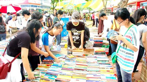 Bạn đọc trẻ chọn sách trong quầy sách giảm giá được sắp xếp ngay ngắn