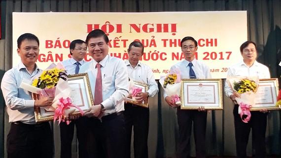 Ông Nguyễn Thành Phong, Chủ tịch UBND TPHCM trao bằng khen của Thành phố cho các đơn vị có đóng góp lớn vào nguồn thu ngân sách. Ảnh:VGP