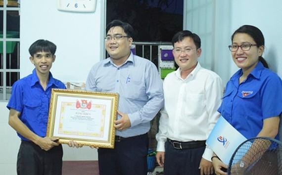 Ông Ngô Minh Hải, Phó Bí thư Thành Đoàn TP HCM, trao bằng khen cho anh Hoàng Trọng Khánh. Ảnh: NLĐO