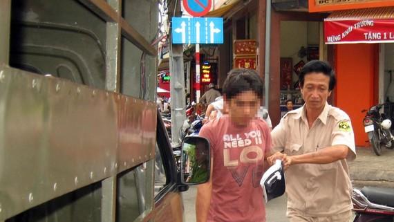 Bảo vệ dân phố đang dẫn giải tên trộm về cơ quan công an