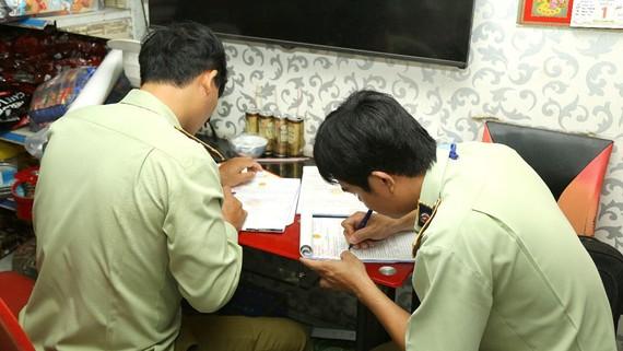 Lực lượng chức năng lập biên bản xử lý vi phạm tại một cửa hàng kinh doanh thuốc lá điếu nhập lậu