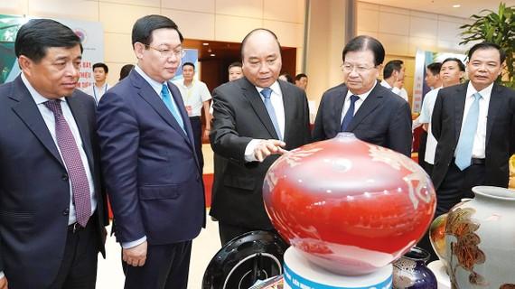 Thủ tướng Nguyễn Xuân Phúc tham quan các gian hàng trưng bày sản phẩm trong khuôn khổ hội nghị Ảnh: VIẾT CHUNG