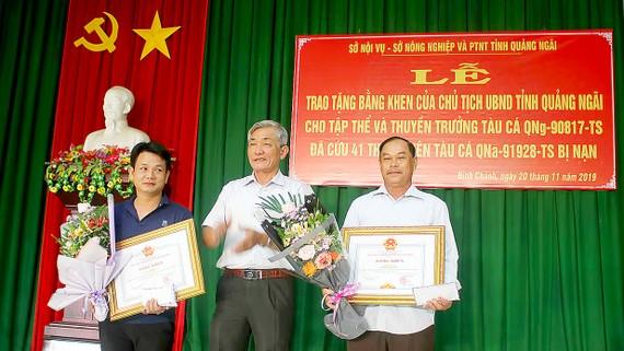 Thuyền trưởng Bùi Văn Danh (bên trái) và đại diện tập thể tàu cá QNg 90817 TS nhận bằng khen