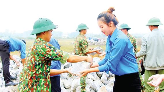 Đoàn viên thanh niên huyện Mỹ Đức hỗ trợ lực lượng quân đội xây dựng tường rào sân bay Miếu Môn. Ảnh: ĐỖ TRUNG