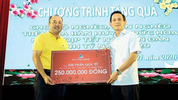 Ông Lương Trí Thảo - Phó TGĐ Tập đoàn Đất Xanh (áo vàng, bên trái), đại diện Tập đoàn trao tặng 500 phần quà Tết đến chính quyền huyện Đức Hòa, tỉnh Long An