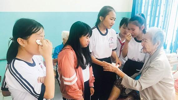 Các em học sinh Trường THCS Văn Thân thăm tết các cụ già ở Trung tâm Nuôi dưỡng bảo trợ người già và tàn tật Thạnh Lộc xúc động khi thấy bà Lê Thị Phượng không có người thân