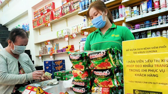 Nhân viên siêu thị dùng khẩu trang khi giao dịch với khách hàng. Ảnh: HOÀNG HÙNG