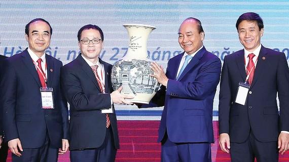 Thủ tướng Nguyễn Xuân Phúc trao quà lưu niệm tặng Trường Đại học Y Hà Nội. Ảnh: TTXVN
