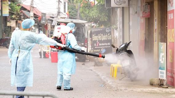 Lực lượng phun hóa chất tiêu độc khử trùng tại thôn Hạ Lôi. Ảnh: QUANG PHÚC