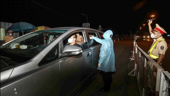 Kiểm tra thân nhiệt ở chốt cầu Đồng Nai vào TPHCM lúc 0 giờ ngày 8-4. Ảnh: DŨNG PHƯƠNG