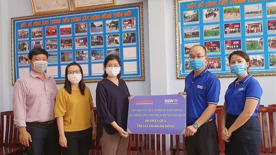 Đại diện Công đoàn BIDV trao tượng trưng cho đại diện Ban Biên tập Báo SGGP 400 phần quà giúp người nghèo vượt khó. Ảnh: LÊ NHUNG