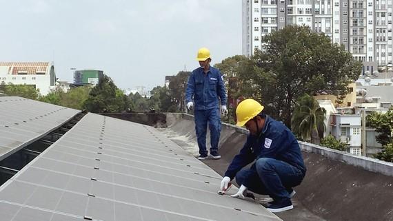 Nhân viên EVNHCMC lắp đặt điện mặt trời trên mái nhà cho một đơn vị thuộc ngành điện lực