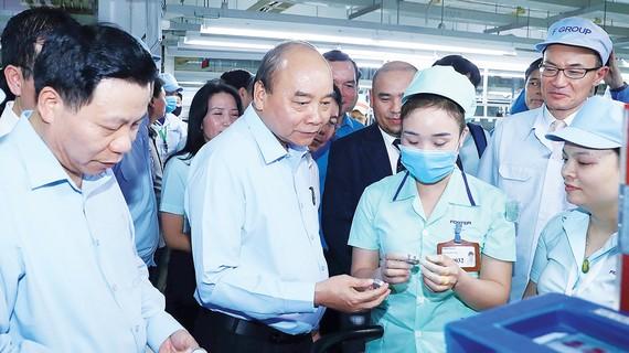 Thủ tướng Nguyễn Xuân Phúc tìm hiểu đời sống công nhân của Công ty TNHH điện tử Foster (Bắc Ninh). Ảnh: TTXVN