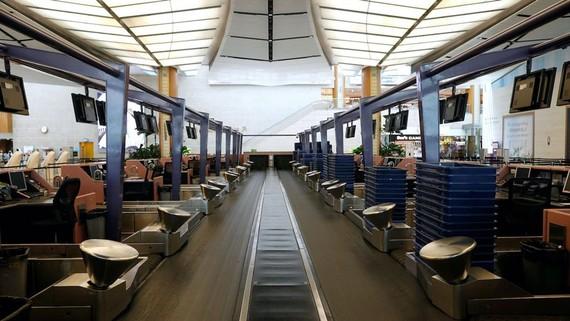 Một băng chuyền hành lý chạy giữa các hàng của quầy làm thủ tục trống tại sân bay Changi ở Singapore. Nguồn: Reuters