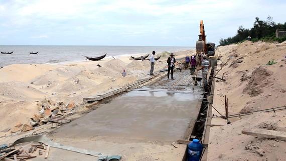 Công nhân hối hả thi công tuyến kè chống sạt lở bờ biển Thừa Thiên - Huế. Ảnh: VĂN THẮNG