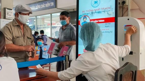 Người bệnh và thân nhân ra vào Bệnh viện Thống Nhất được kiểm tra thân nhiệt và khai báo y tế Ảnh: HOÀNG HÙNG