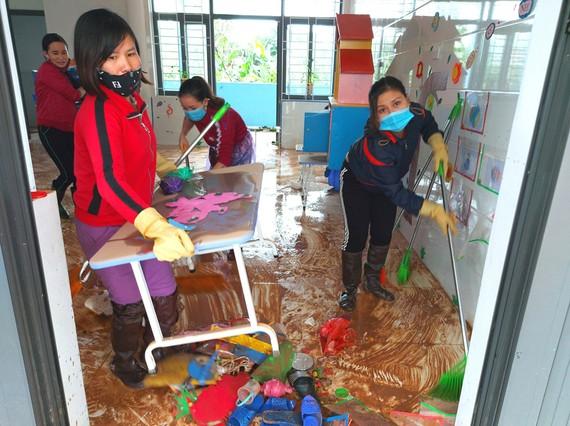 Giáo viên vùng lũ huyện Cẩm Xuyên, Hà Tĩnh dọn vệ sinh trường lớp sau lũ. Ảnh: DƯƠNG QUANG