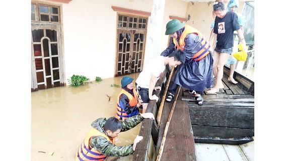 Cán bộ xã Tân Ninh giúp dân lên thuyền chạy lũ