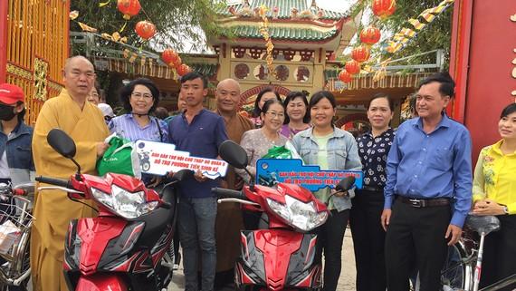 Thượng tọa Thích Huệ Công (bìa trái) trao quà động viên người nghèo và kêu gọi người dân tham gia bảo vệ môi trường. Ảnh: THÁI PHƯƠNG