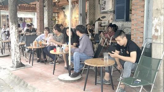 Nhiều bạn trẻ không đeo khẩu trang tại một quán cà phê
